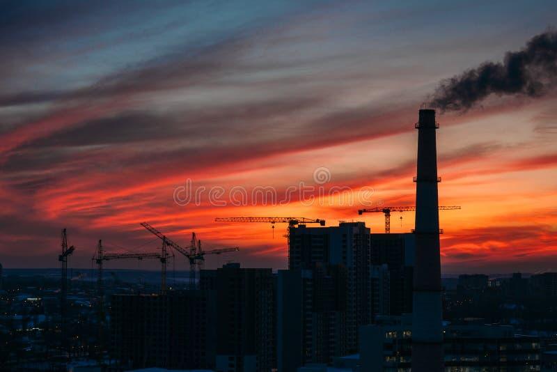 城市日落起重机、高层建筑物和建造场所全景和剪影有烟的 库存照片