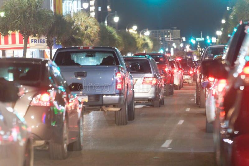 城市汽车通行在晚上,在路的队列 免版税库存照片