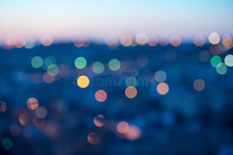 城市点燃在蓝色背景的抽象圆bokeh 免版税库存照片