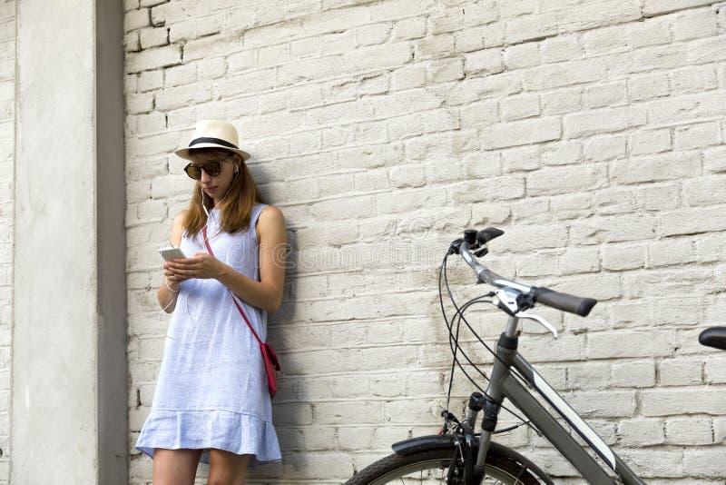 城市生活概念 站立在白色砖墙旁边的少妇听到在耳机的音乐 免版税图库摄影