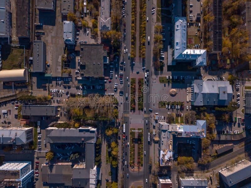 城市的一张顶视图在一个晴朗的夏日,在铁屋顶房子,高层建筑物,绿色和黄色树,主要 库存图片