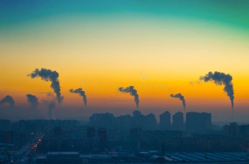 城市的工业风景的晚上视图有黑烟排放的从在日落的烟囱图片