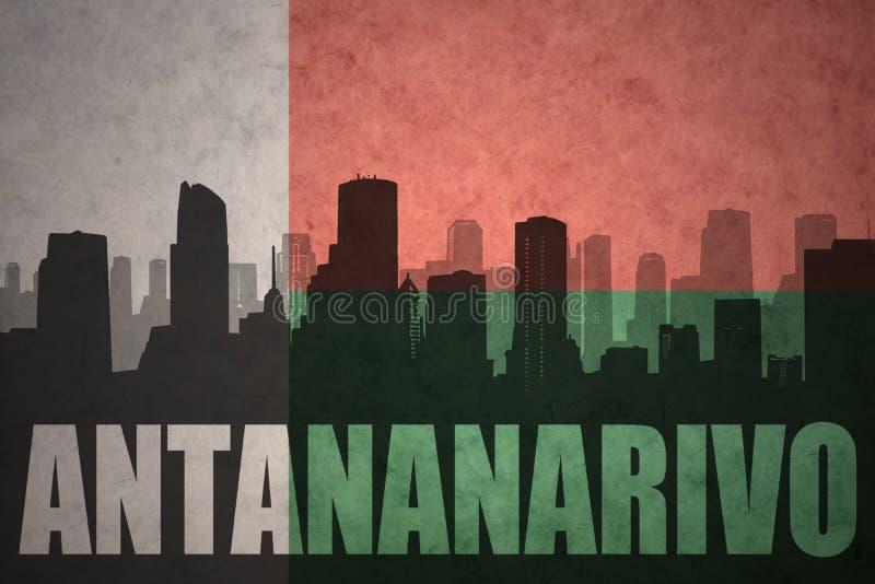 城市的抽象剪影有文本的安塔那那利佛在葡萄酒马达加斯加旗子 免版税图库摄影