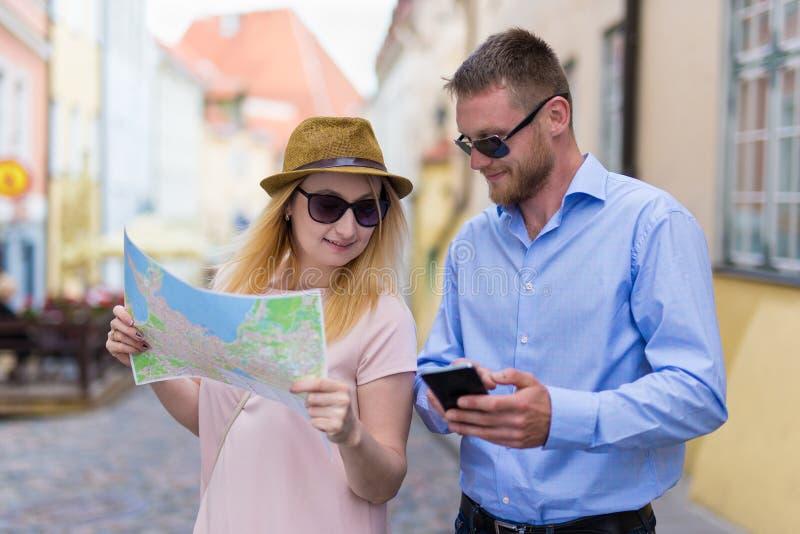 城市的游人绊倒使用智能手机和城市地图 免版税库存图片