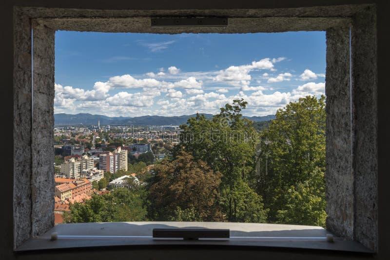 城市的看法通过其中一卢布尔雅那,斯洛文尼亚城堡的窗口/发射孔  免版税库存照片