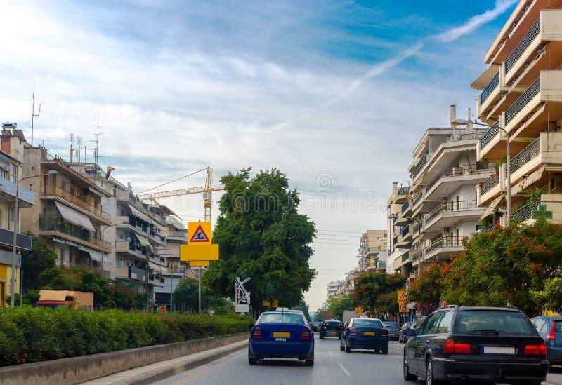 城市的视图 移动在街道下的汽车 在街道的边是高层建筑物 在天际的大起重机 免版税库存图片