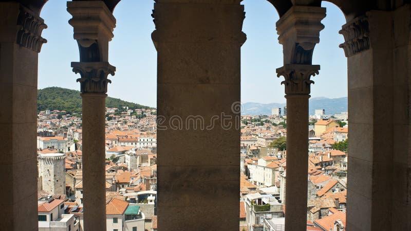 城市的风景鸟瞰图通过从钟楼的石窗口,房子屋顶在老镇,美好的都市风景,晴朗 库存照片