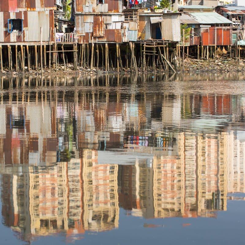 城市的贫民窟的看法从河的 在新的高层建筑物的水反射 库存照片