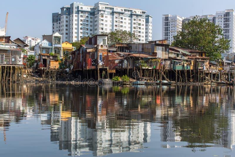 城市的贫民窟的看法从河的(在背景中和新的大厦的反射) 免版税库存图片