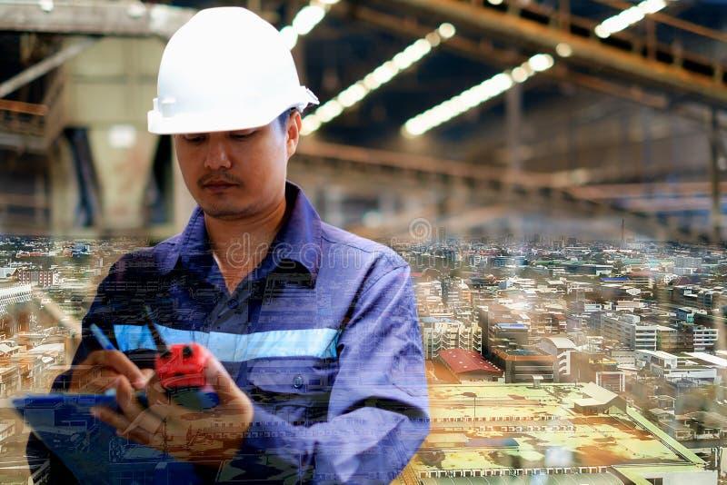 城市背景和工程师两次曝光有一致和白色安全帽的 免版税库存图片