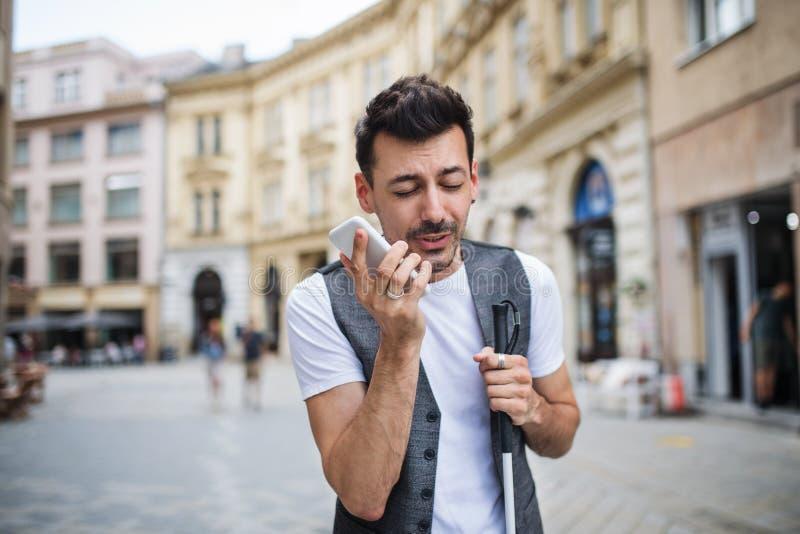 城市街头年轻盲人带智能手机打电话 免版税库存照片