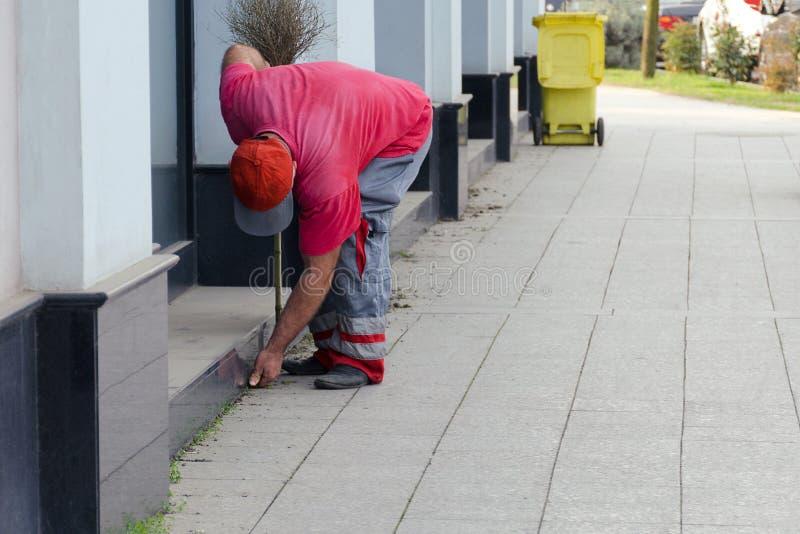 城市街道的清洁-工作者制服的围场老板用人工收集垃圾在大厦附近 免版税库存图片
