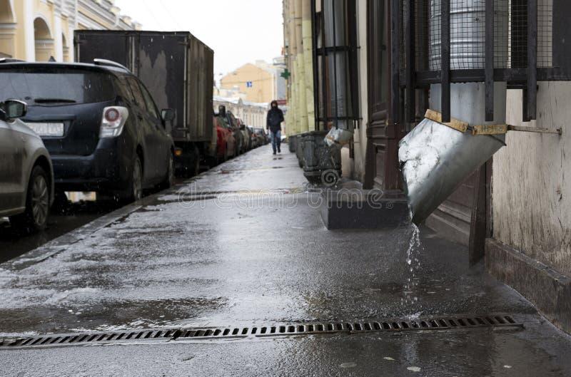 城市街道,走在边路,雨,汽车的人停放 库存图片