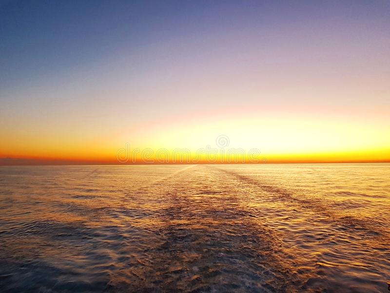 城市视图和日落天空 幻想天空 在水喷气机的背景的日落从一艘移动的船的推进器的 免版税库存照片