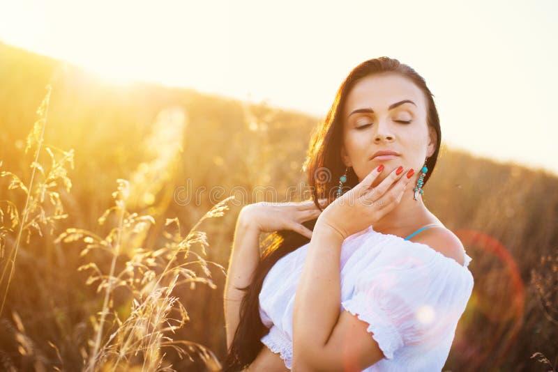域的美丽的妇女在日落 图库摄影