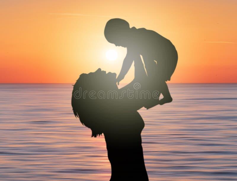 培养她的孩子儿子的母亲在与太阳的日落在中部 免版税图库摄影