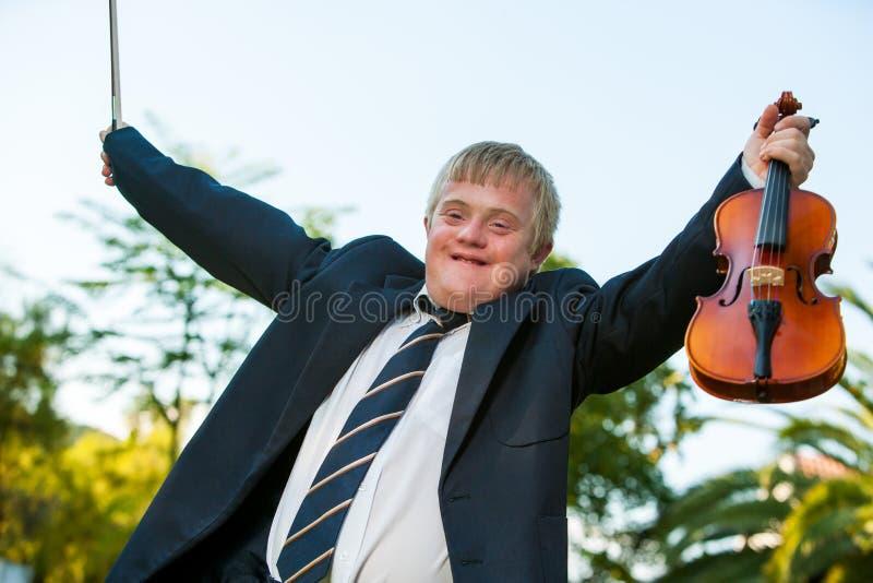 培养小提琴的友好有残障的男孩户外。 图库摄影