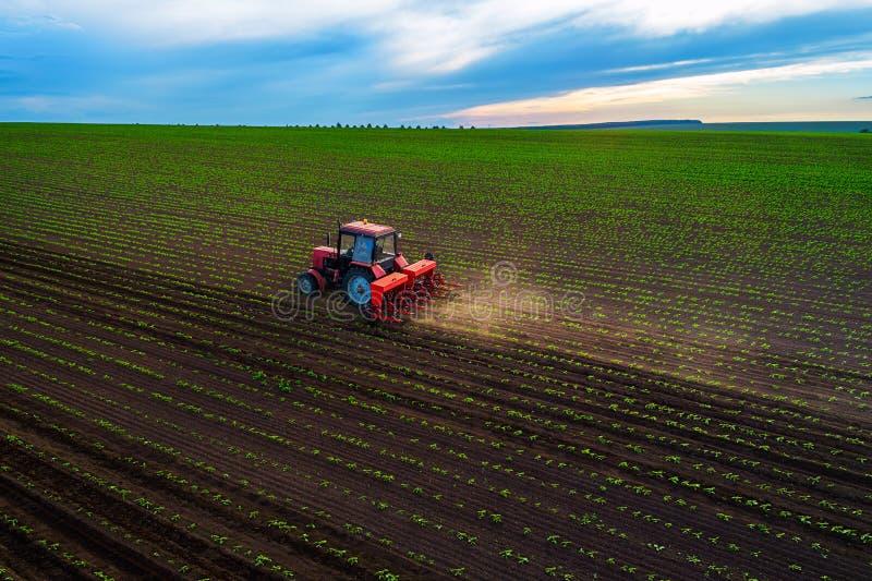 培养领域的拖拉机在春天,鸟瞰图 免版税库存图片