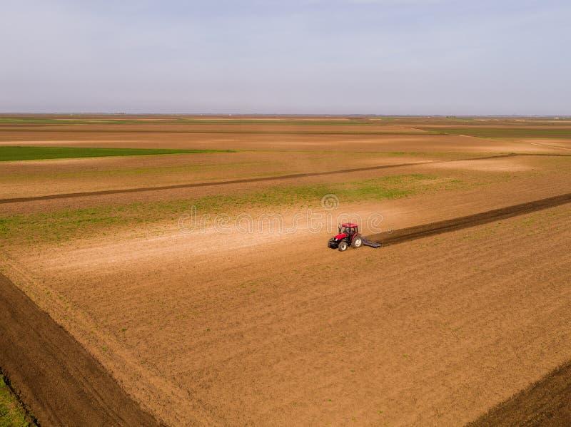 培养领域的拖拉机的空中射击在春天 库存图片