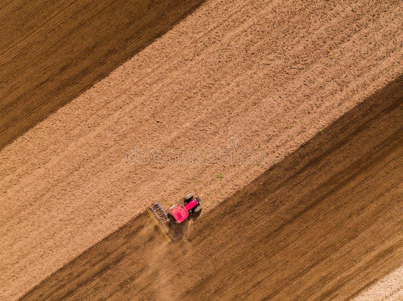 培养领域的拖拉机的空中射击在春天 免版税库存图片