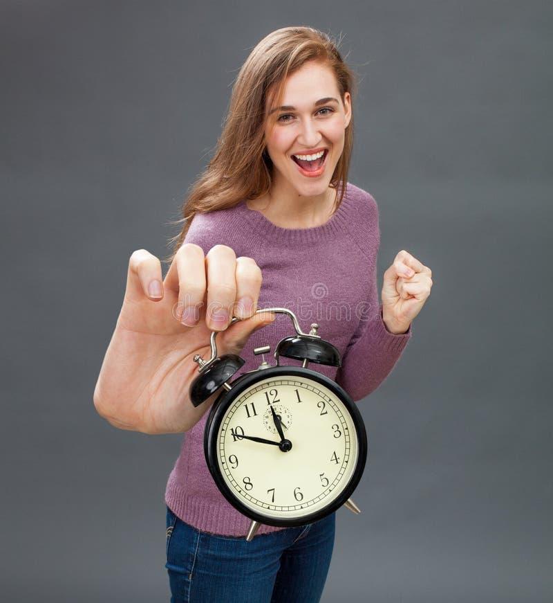 培养乐观的闹钟和赢取最后期限的激动的妇女 免版税库存照片