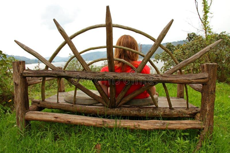 基于一个大长木凳的妇女 免版税库存图片