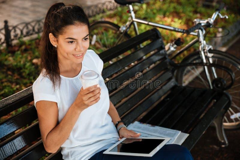 基于与咖啡的长凳的妇女在公园 库存图片