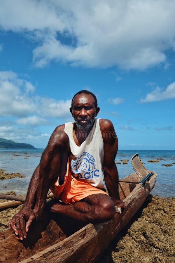 基于他的舷外浮舟的渔夫在热带南太平洋海洋的惊人的岸 免版税库存照片