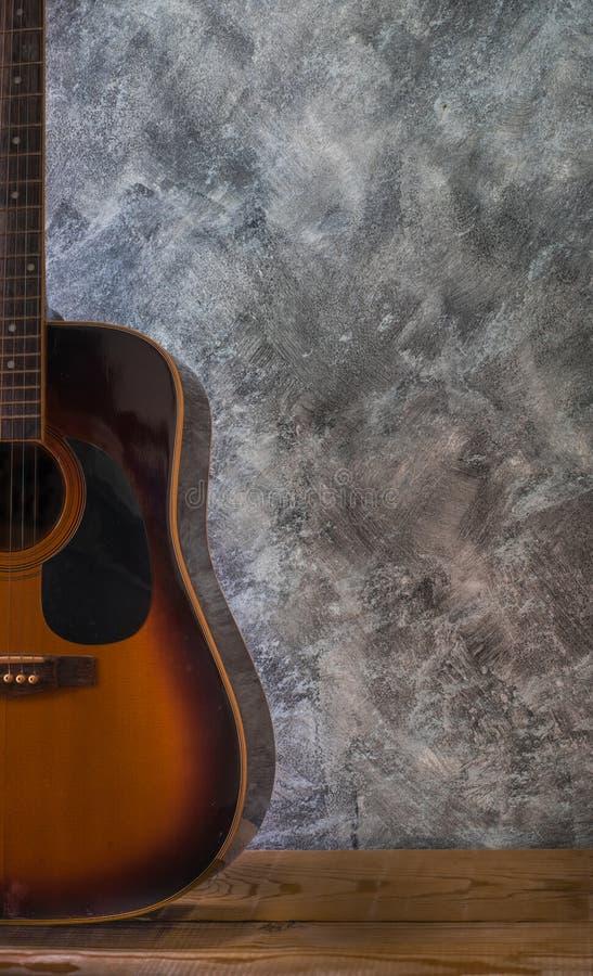 基于反对木桌空白的水泥墙壁的声学吉他 库存图片