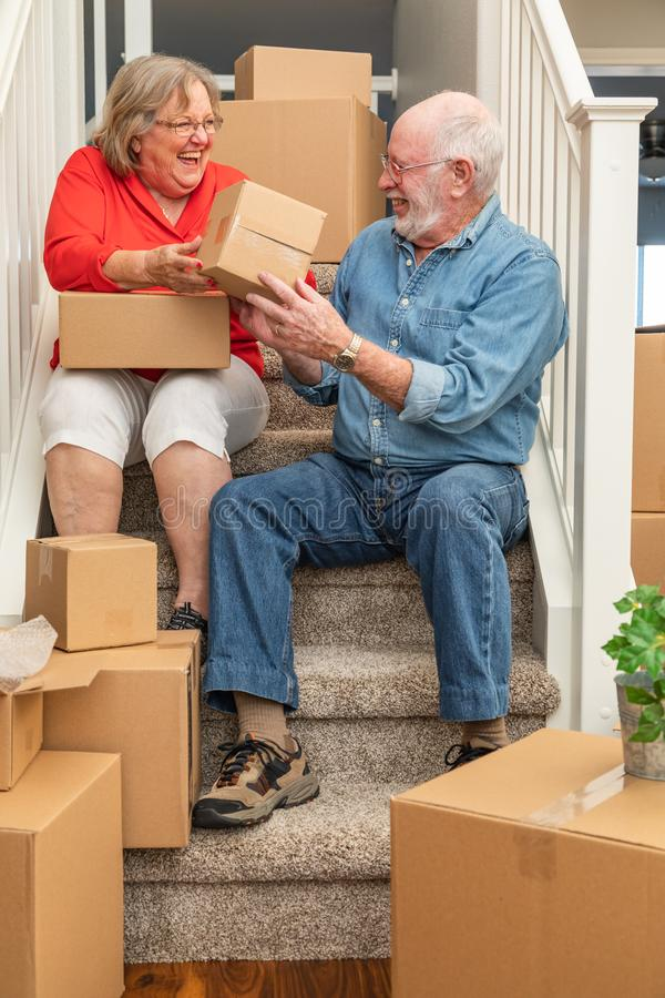 基于台阶的笑的资深夫妇围拢通过移动箱子 免版税库存照片