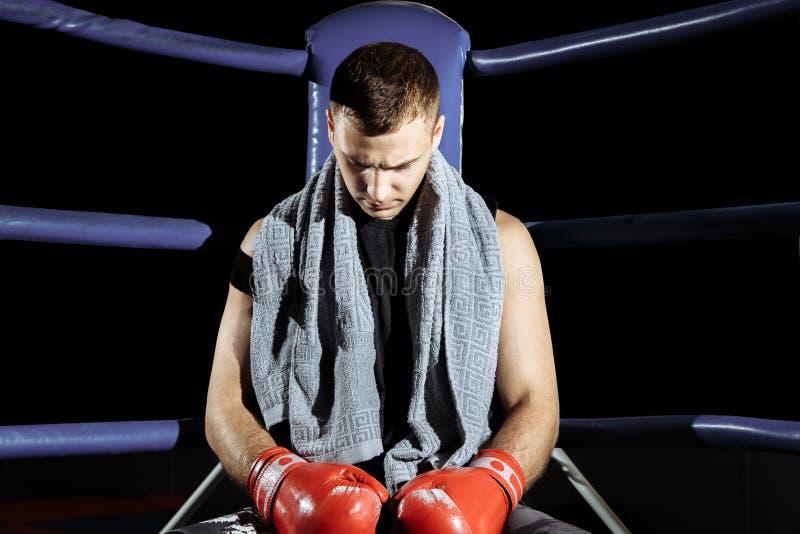 基于在圆环的角落的绳索的肌肉专业反撞力拳击手,当训练为下次比赛时 免版税库存图片