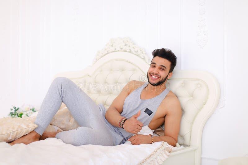基于在床上的困难的天的年轻阿拉伯人画象在明亮 免版税图库摄影