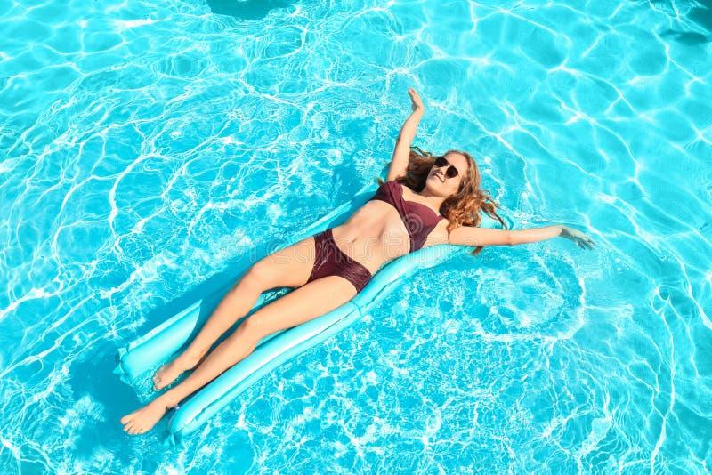 基于在水池的可膨胀的床垫的美丽的年轻女人 免版税库存照片