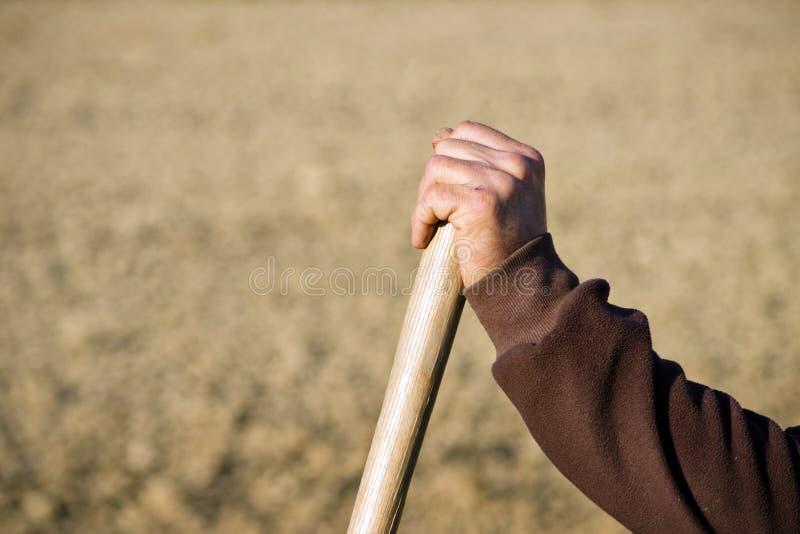 基于木铁锹或犁耙夹子的农夫手 库存照片