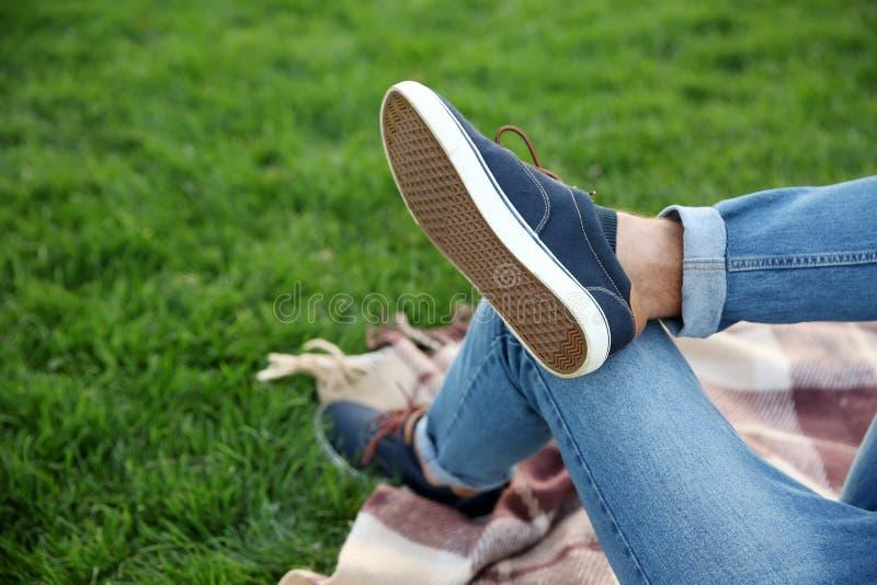 基于格子花呢披肩的年轻人的腿在公园 免版税库存图片