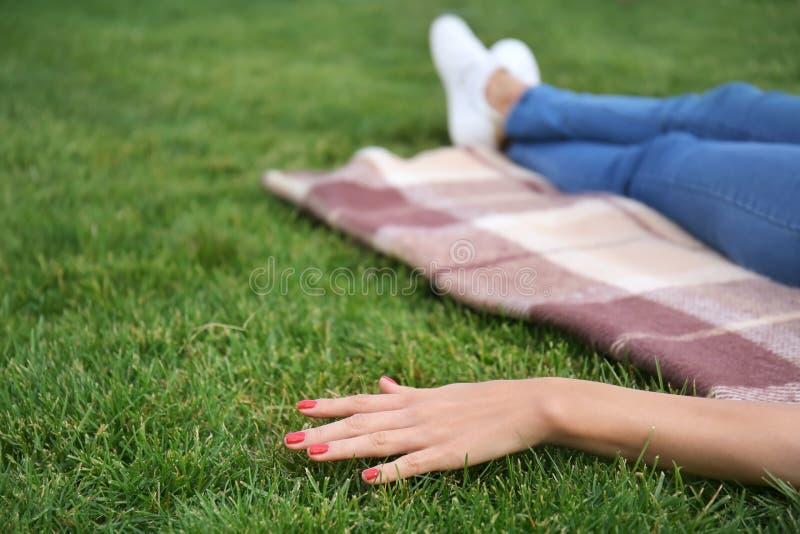 基于格子花呢披肩的年轻女人在公园 免版税库存照片