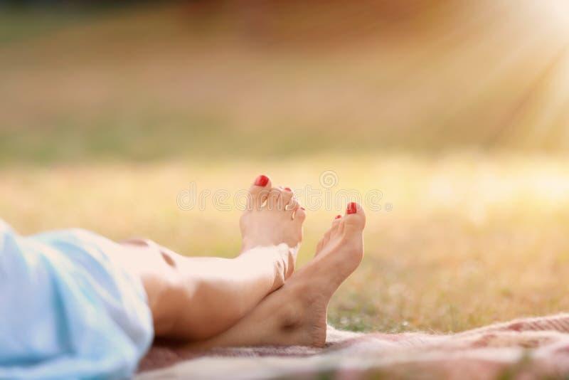 基于格子花呢披肩的年轻女人的腿在公园 免版税库存照片