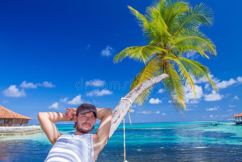 基于海滩棕榈树的华美的人 免版税库存图片