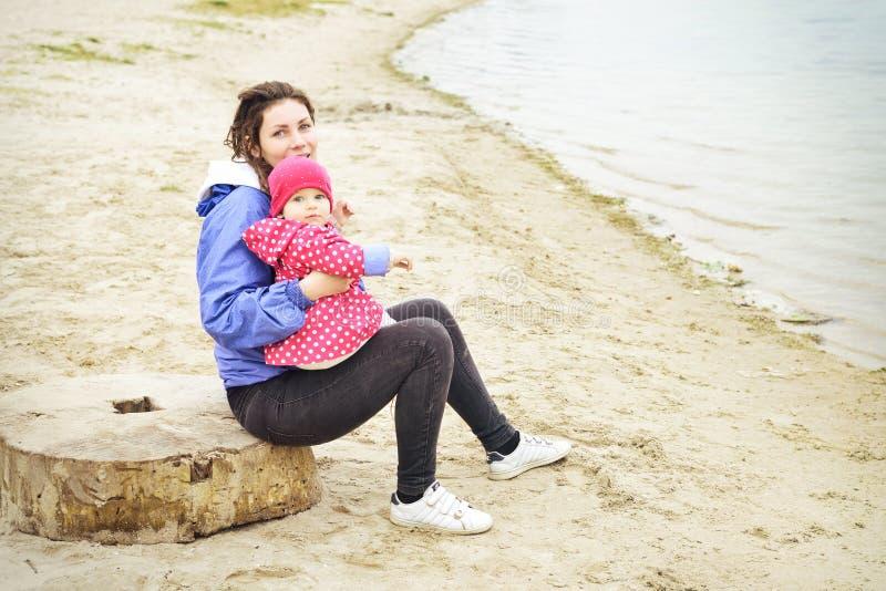基于海滩的愉快的快乐的家庭画象  笑的面孔,举行可爱的儿童女婴和拥抱的母亲 免版税库存图片