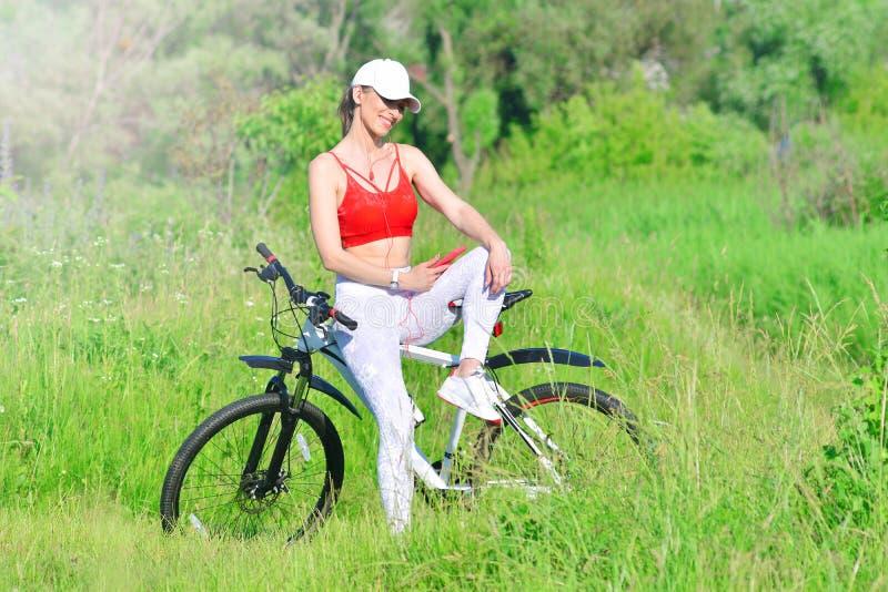 基于自行车户外和享受听到从智能手机的音乐的女孩 图库摄影
