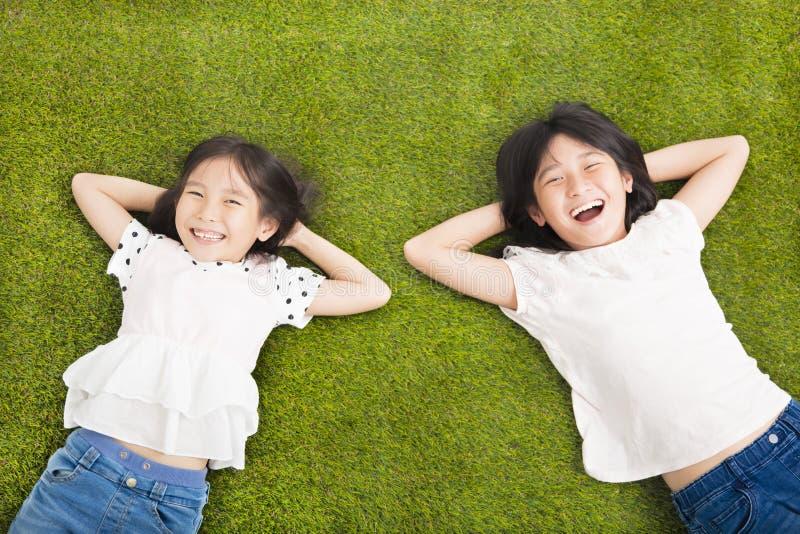 基于草的愉快的小女孩 库存照片