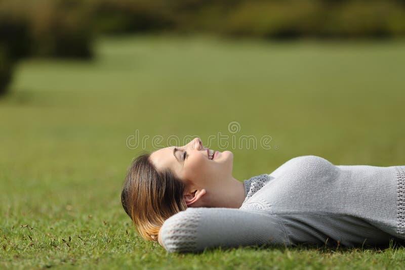 基于草的美丽的妇女在公园 免版税库存图片