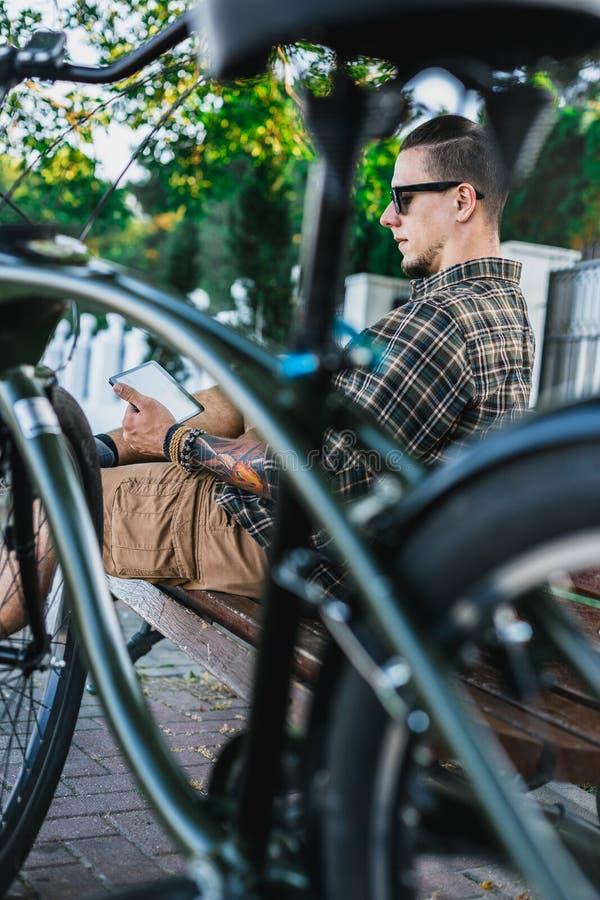 基于长凳在自行车附近和使用片剂通信连接数字式设备技术概念的骑自行车者人 库存图片