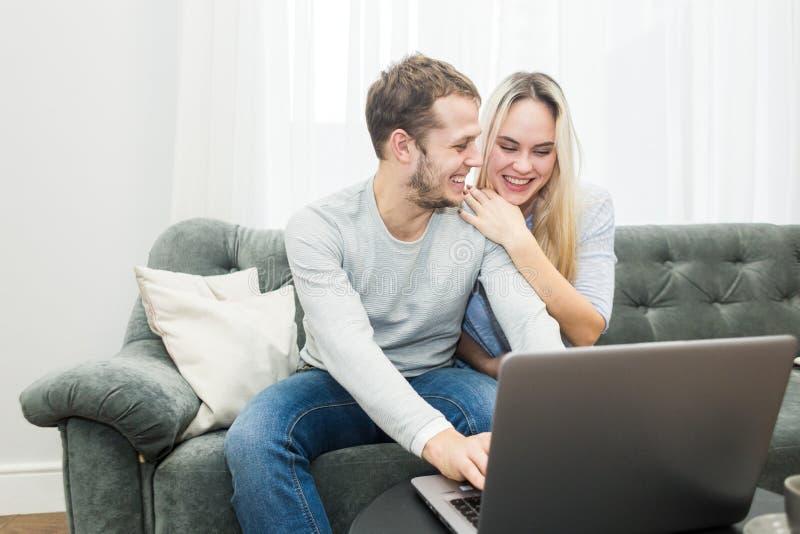 基于长沙发和观看的网上录影的年轻美好的夫妇从一台膝上型计算机在客厅 免版税库存图片