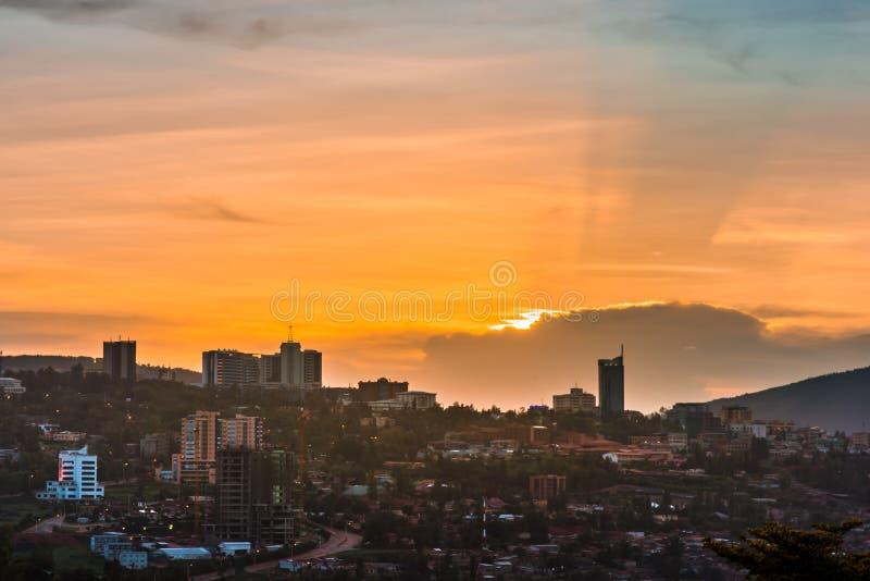 基加利市中心地平线和周边地区在五颜六色的云彩下在日落 卢旺达 免版税库存照片