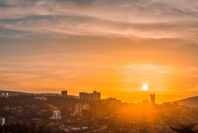 基加利市中心地平线和周边地区在金黄天空下在日落 免版税图库摄影
