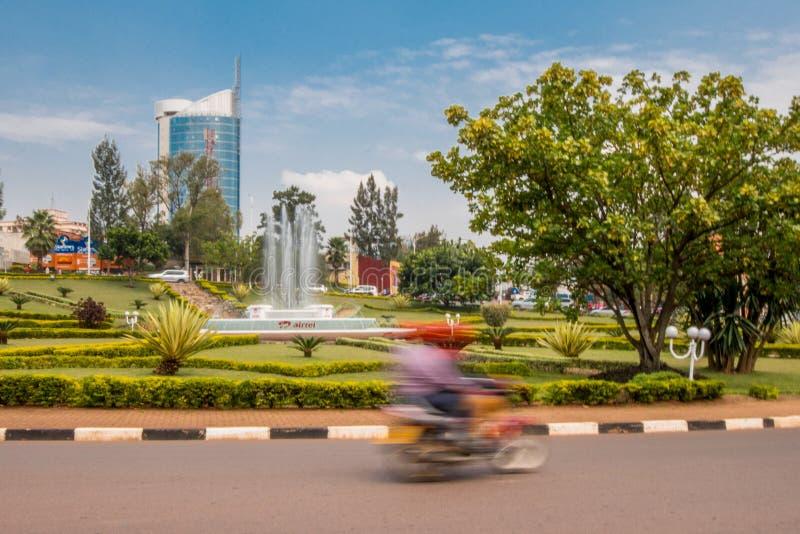 基加利,卢旺达- 2018年9月20日:在环形交通枢纽的一辆` moto `摩托车在市中心附近,与基加利在后面的市塔 库存照片