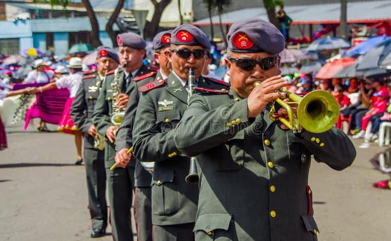 基多,厄瓜多尔- 2018年1月31日:在节日游行期间,未认出的goup人佩带的贝雷帽和使用吹小号 免版税库存图片