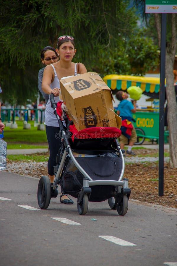 基多,厄瓜多尔- 2016年4月, 17日:有一个纸板箱子的未认出的妇女用里面食物,提供救灾食物,穿衣 图库摄影