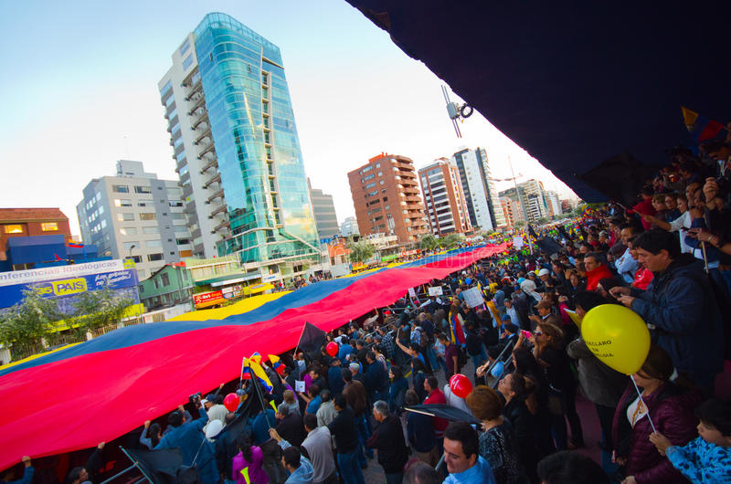 基多,厄瓜多尔- 2016年4月7日:显示一面非常大厄瓜多尔旗子、抗议标志和新闻工作者的人 免版税库存照片